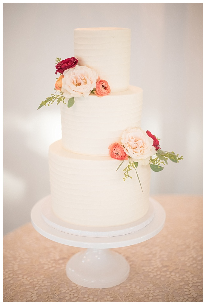white-three-tiered-wedding-cake-pink-and-peach-flowers-mikkel-paige-photography