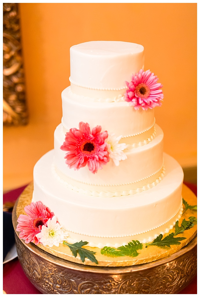 white-wedding-cake-with-pink-gerber-daisies-casey-fatchett-photography