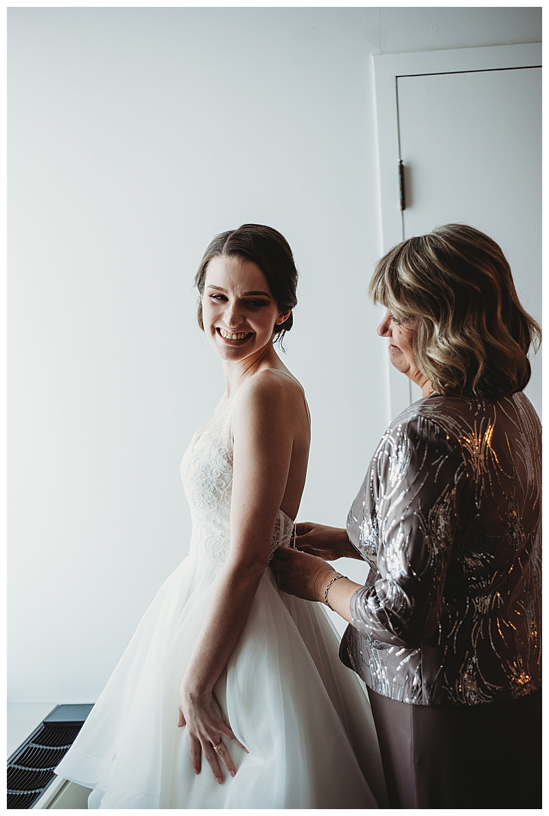mother-putting-on-daughters-wedding-dress