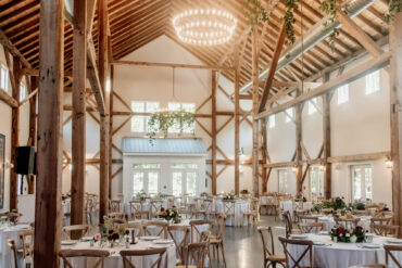 Barn Wedding Reception with Exposed Beam Cathedral Ceiling and Greenery Chandeliers